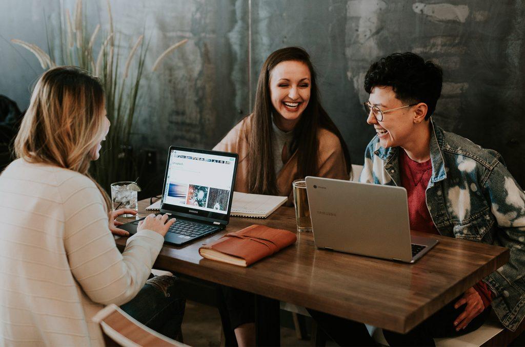 tre donne nomadi digitali intorno a un tavolo lavorando