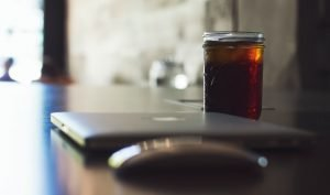 Un Macbook con un magic mouse e un caffè filtrato in un bar per lavorare