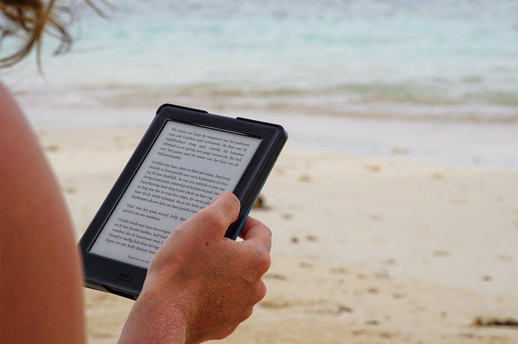 Una donna in spiaggia leggendo un e-reader per ridurre l'impatto ambientale